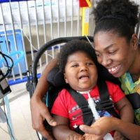 Antoinise Samuels with her 17-month-old son Samuel at their North Miami studio apartment. Samuel was born prematurely with microcephaly. He remains on a respirator and is fed through a G-tube. Samuel has outgrown his infant wheelchair, so transporting him has become increasingly difficult. The family is asking for a toddler wheelchair so he can get the help that might make it possible for him to one day attend school.